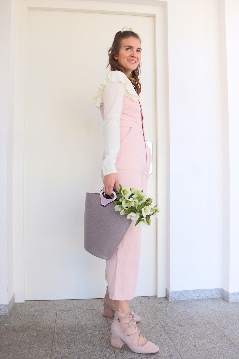 Pink Jumpsuit. Fashion and Style Blog Girl from Heartfelt Hunt. Girl with blonde half-up half-down loose waves and scrunchie wearing a pink jumpsuit, blouse with ruffles, Louis Vuitton bucket bag and lace-up heels.