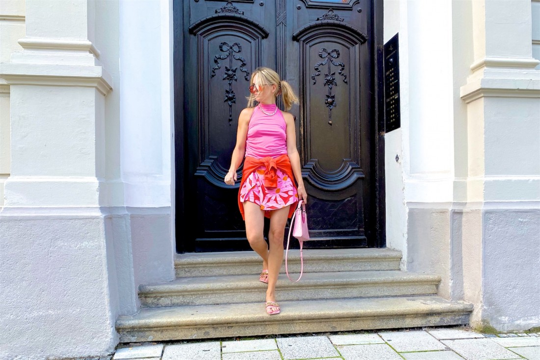 Pink Orange. Fashion Blogger Girl by Style Blog Heartfelt Hunt. Girl with blond hair and pink hair claw clip wearing a pink top, orange sunglasses, orange hoodie, floral skirt, pink Staud bag and pink sandals.