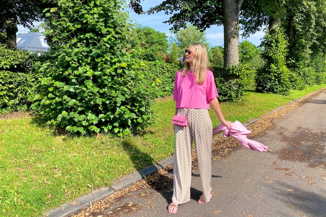 Pink Polka Dots. Fashion Blogger Girl by Style Blog Heartfelt Hunt. Girl with blond hair wearing a pink tee, polka dot pants, pink mini bag, pink sweatshirt and pink sandals.