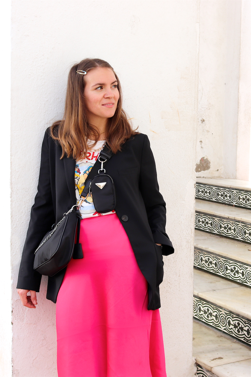 Pink Skirt. Fashion Blogger Girl by Style Blog Heartfelt Hunt. Girl with blond hair wearing a blazer, graphic tee, statement necklace, pink skirt, bag and chunky sneakers.