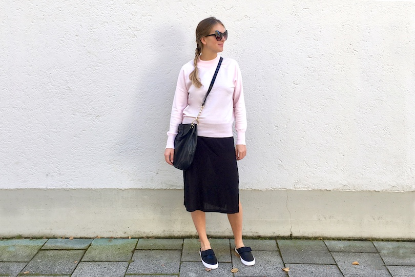 Pink Sweater. Fashion Blogger Girl by Style Blog Heartfelt Hunt. Girl with blond dutch braid wearing a black dress, pink sweater, Michael Kors bag, cat eye sunglasses and mule sneakers with a bow.