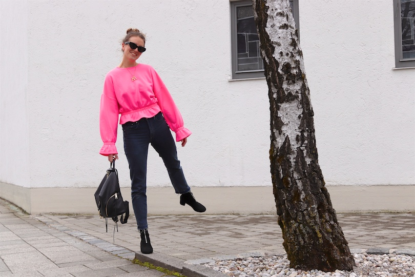 Pink Sweater. Fashion and Style Blog Girl from Heartfelt Hunt. Girl with blonde, high, messy bun wearing a pink sweater, mom jeans, slim sunglasses, Rebecca Minkoff backpack and sock boots.