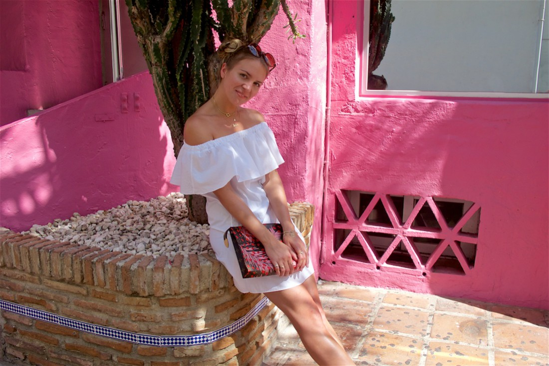 Pink Wall. Fashion Blogger Girl by Style Blog Heartfelt Hunt. Girl with two blond, high knots wearing a white off-shoulder dress, Louis Vuitton bag, round sunglasses and leopard sandals.