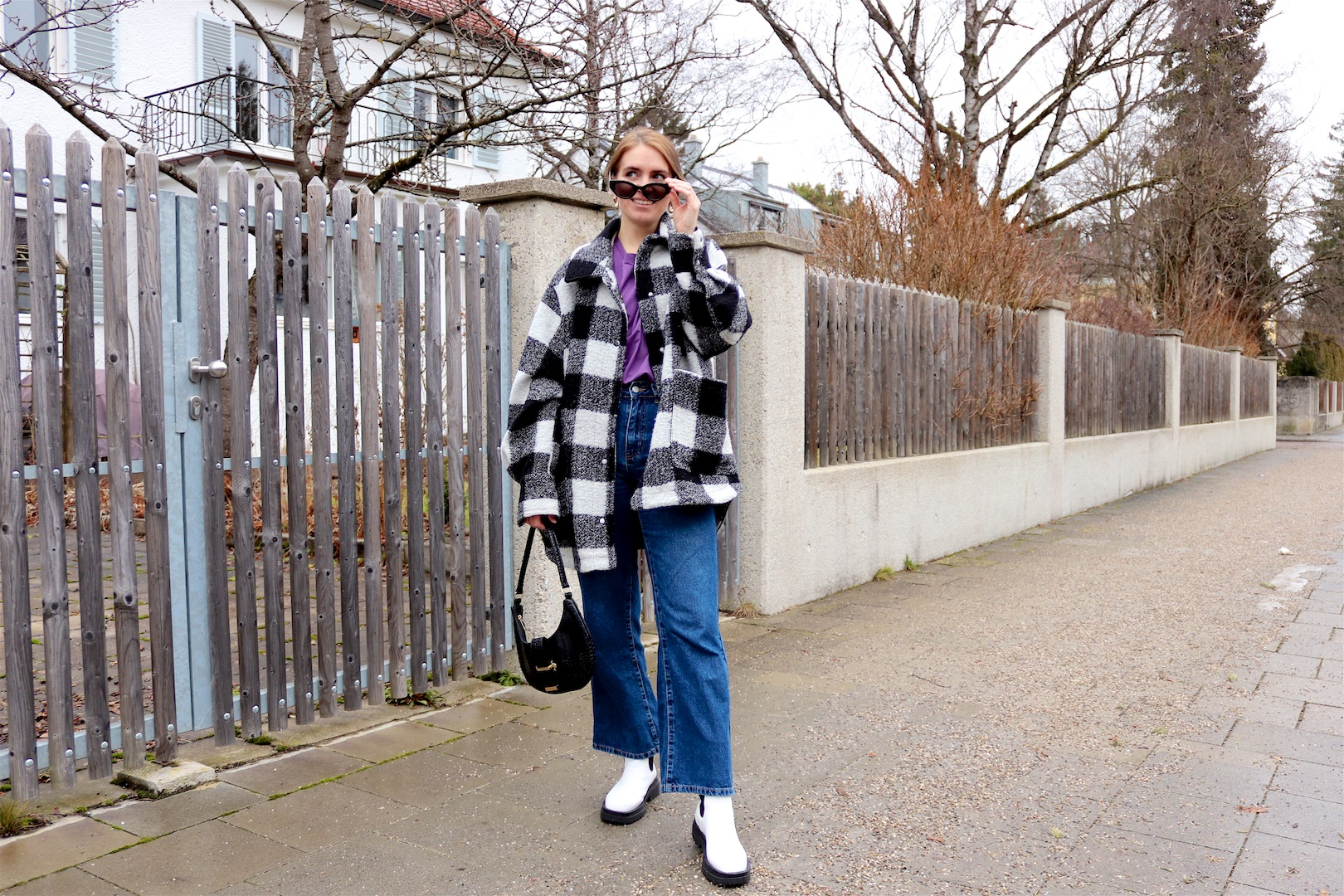 Plaid & Purple. Fashion Blogger Girl by Style Blog Heartfelt Hunt. Girl with blond low bun wearing a plaid jacket, purple tee, wide leg jeans, slim sunglasses, 90s bag and white boots.