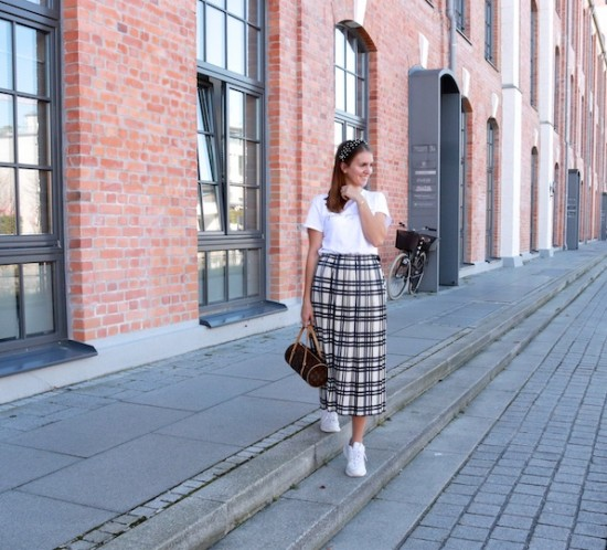 Pleated Tartan. Fashion Blogger Girl by Style Blog Heartfelt Hunt. Girl with blond hair and a velvet headband with pearls wearing a statement tee, pleated tartan skirt, Louis Vuitton bag and white, chunky sneakers.