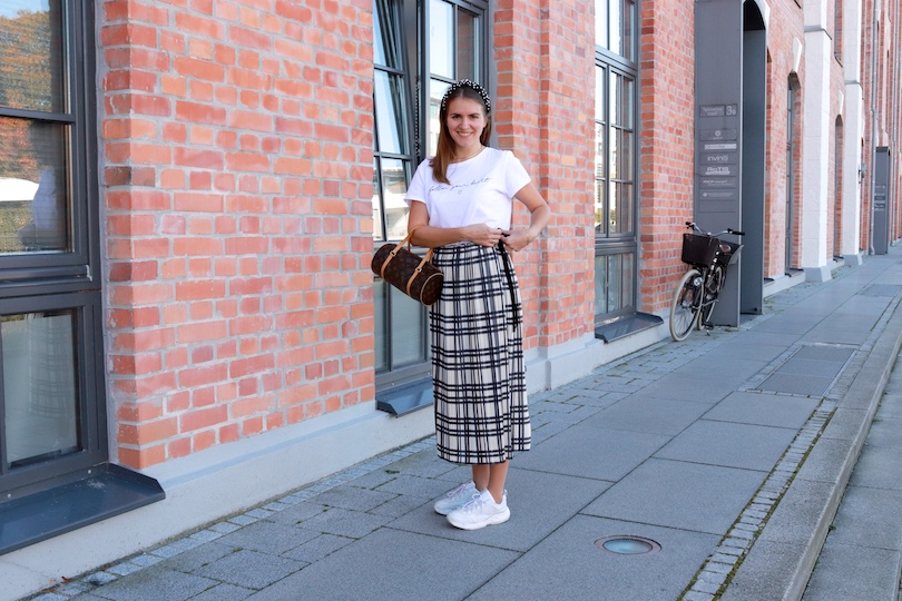 Pleated Tartan. Fashion and Style Blog Girl from Heartfelt Hunt. Girl with blonde hair and a velvet headband with pearls wearing a statement tee, pleated tartan skirt, Louis Vuitton bag and white, chunky sneakers.