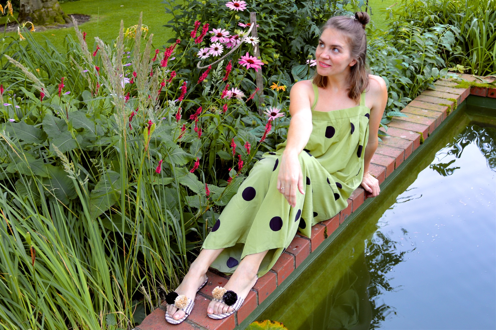 Polka Dot Jumpsuit. Fashion Blogger Girl by Style Blog Heartfelt Hunt. Girl with blond half-up half-down messy bun wearing a polka dot jumpsuit and pompon sandals.
