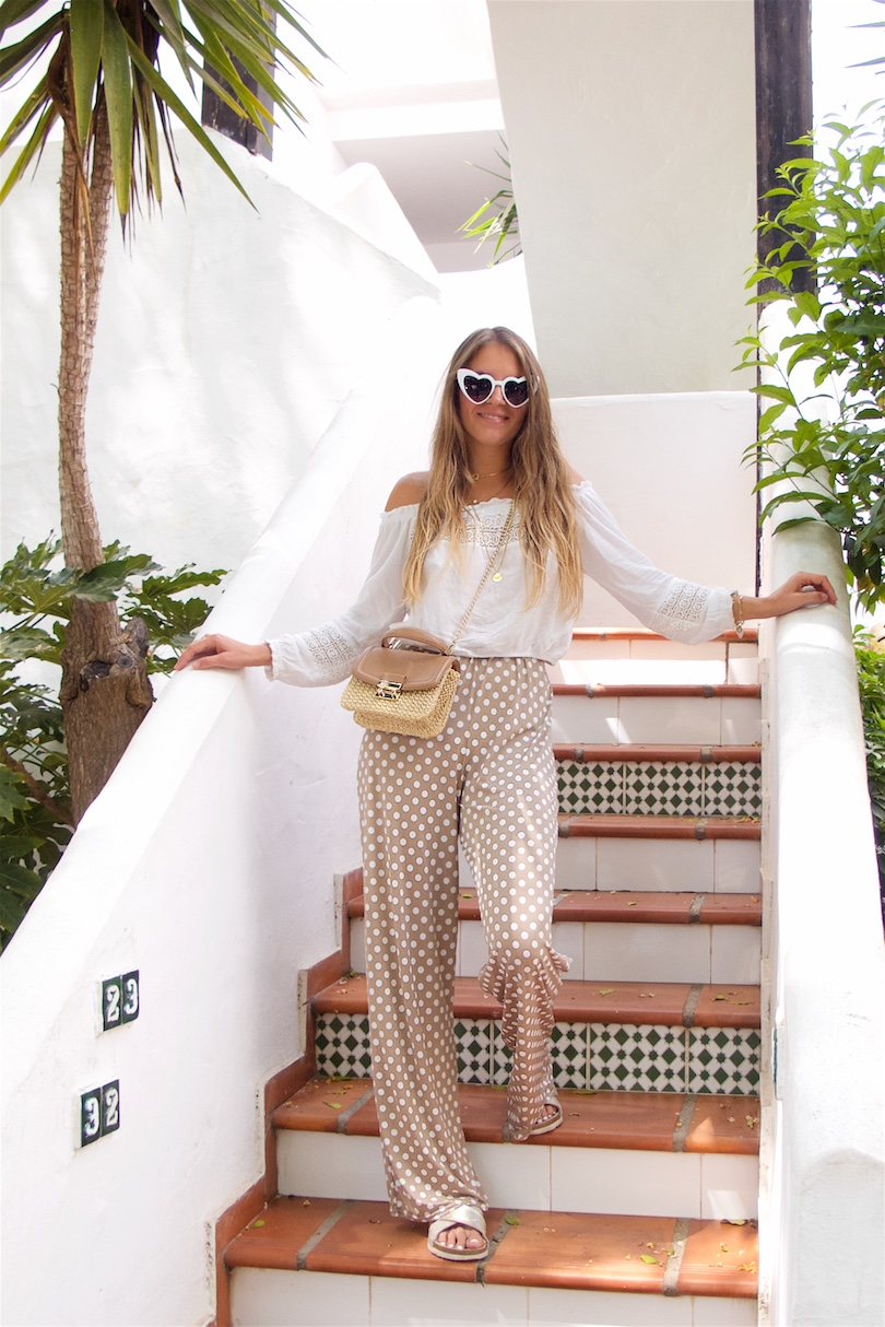 Polka Dot Pants. Fashion and Style Blog Girl from Heartfelt Hunt. Girl with blonde long hair wearing polka dot pants, white off shoulder top, heart shaped sunnies, straw bag and golden flats.
