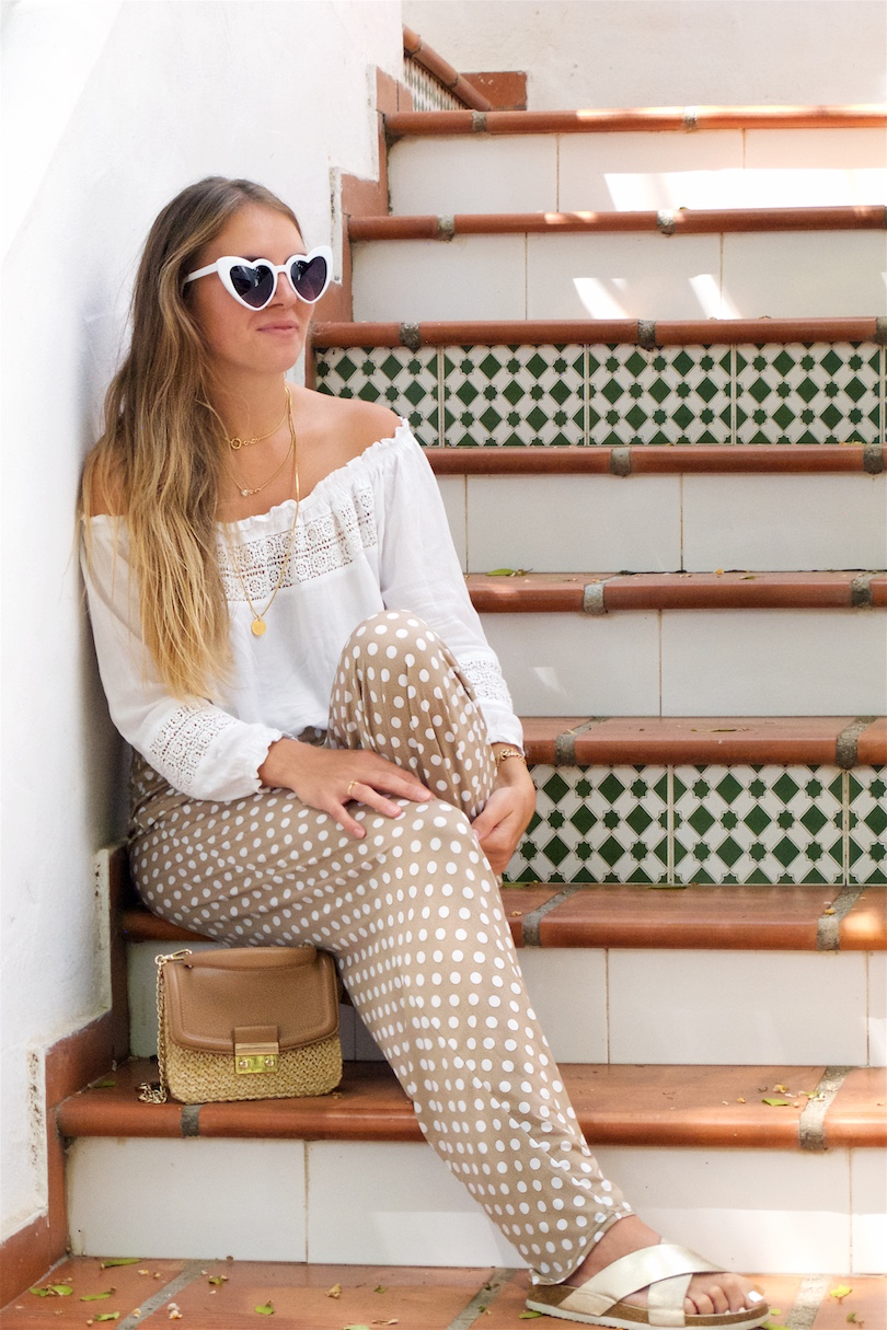 Polka Dot Pants. Fashion Blogger Girl by Style Blog Heartfelt Hunt. Girl with blond long hair wearing polka dot pants, white off shoulder top, heart shaped sunnies, straw bag and golden flats.