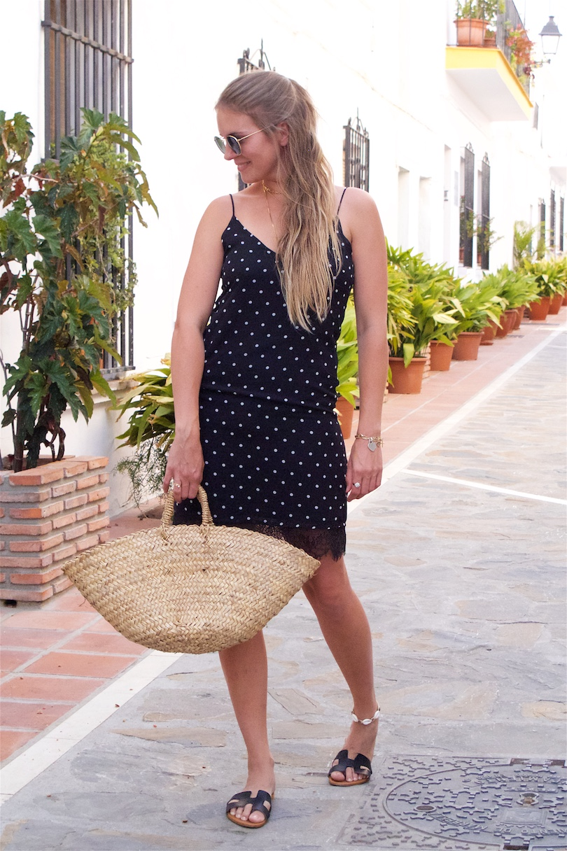 Polka Dot Pieces. Fashion and Style Blog Girl from Heartfelt Hunt. Girl with blonde half-up half-down hairstyle wearing a polka dot dress, Ray-Ban sunglasses, straw bag and black flats showing her favorite polka dot pieces.