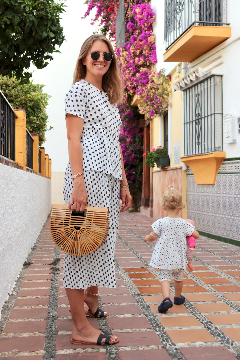 Polka Dot Trouble. Fashion Blogger Girl by Style Blog Heartfelt Hunt. Girl with blond hair wearing a polka dot top, polka dot pants, Ray-Ban sunglasses, bamboo bag and black sandals. She and her little mini me wearing matching mother daughter outfits with polka dot two pieces.