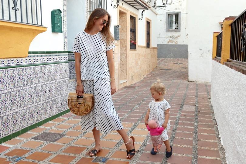 Polka Dot Trouble. Fashion and Style Blog Girl from Heartfelt Hunt. Girl with blonde hair wearing a polka dot top, polka dot pants, Ray-Ban sunglasses, bamboo bag and black sandals. She and her little mini me wearing matching mother daughter outfits with polka dot two pieces.