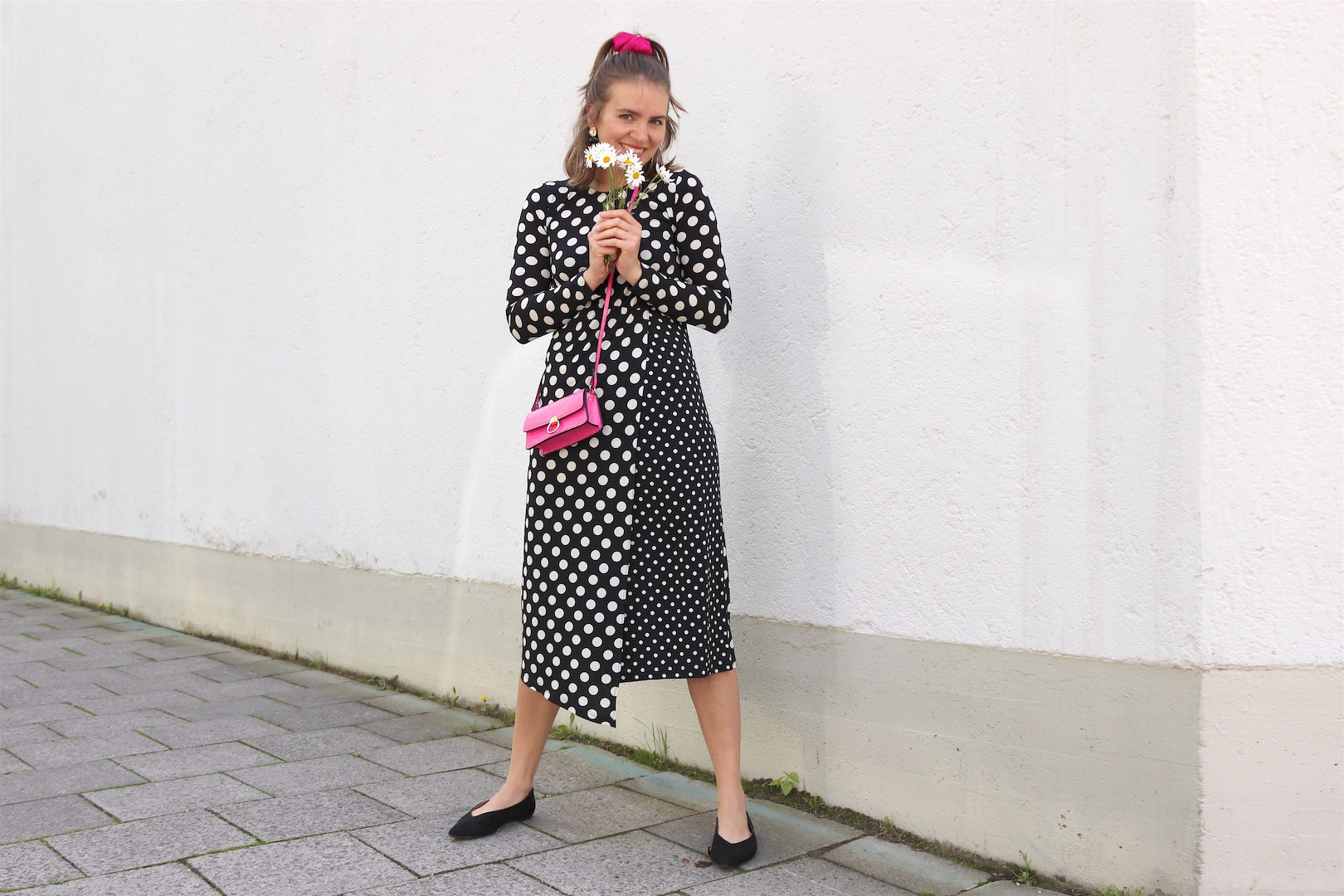 Polka Dots Marguerites. Fashion and Style Blog Girl from Heartfelt Hunt. Girl with blonde half-up half-down hairstyle and pink scrunchie wearing a polka dot dress, gold earrings, pink mini bag and pointed flats.