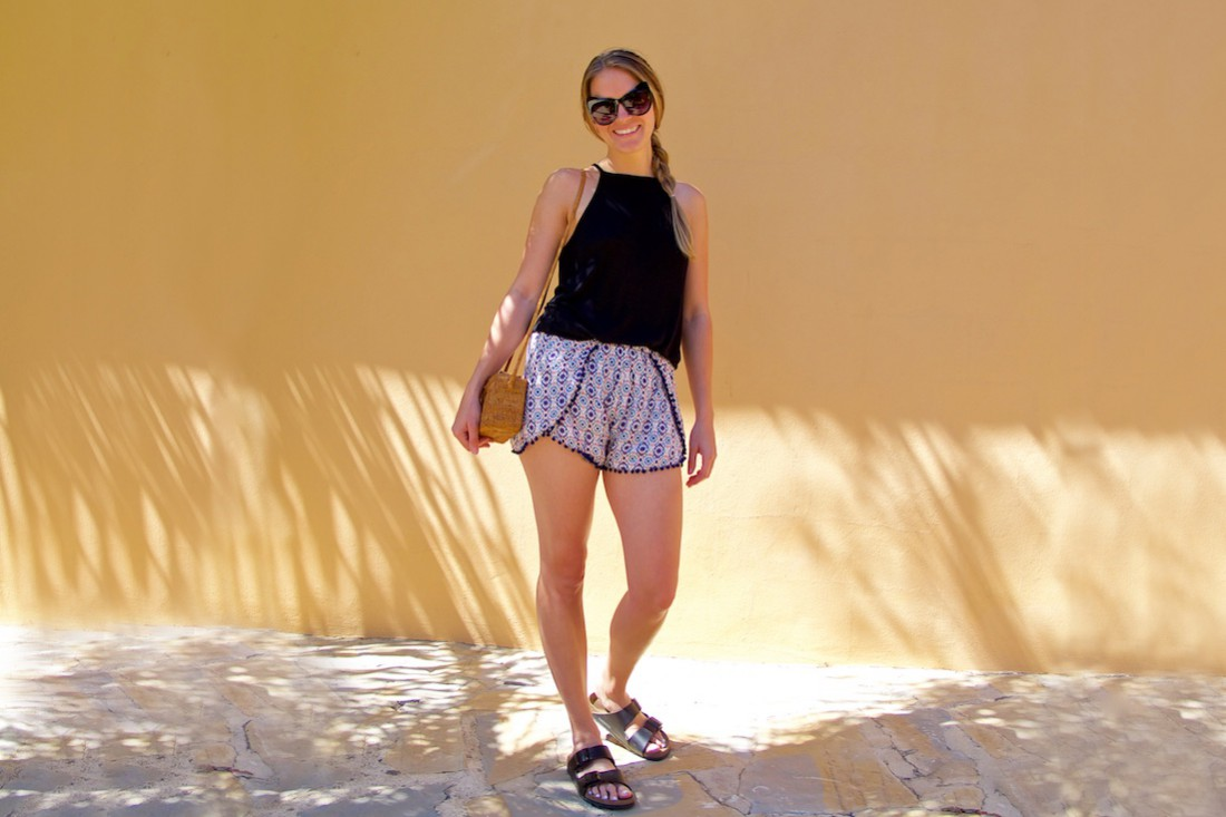 Pompom Shorts. Fashion Blogger Girl by Style Blog Heartfelt Hunt. Girl with blond braid wearing pompom shorts, black dress, cat eye sunglasses, straw bag and Birkenstock sandals.