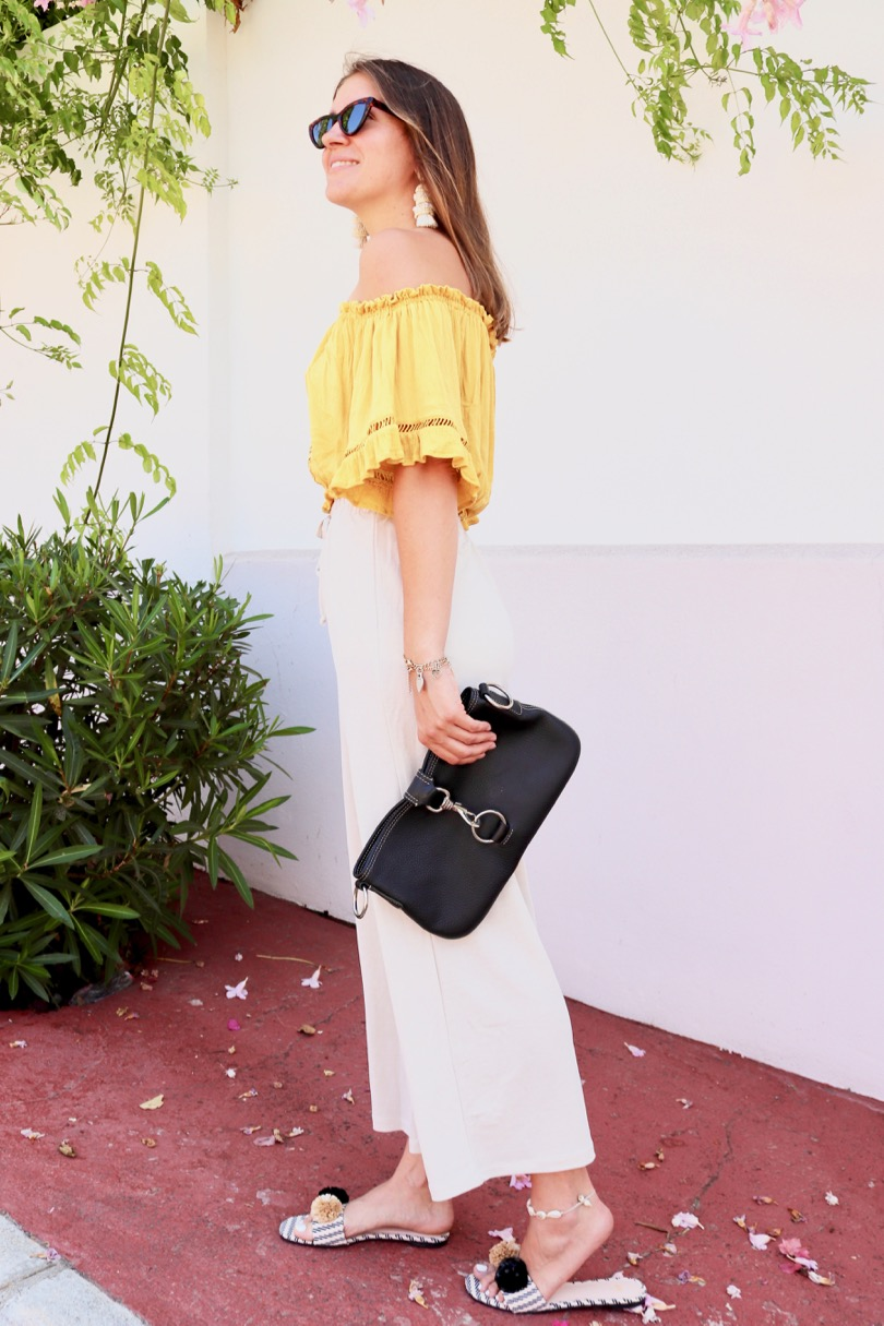 Pompon Straw Sandals. Fashion and Style Blog Girl from Heartfelt Hunt. Girl with blonde hair wearing a yellow off shoulder top, wide pants, tortoise shell sunglasses, tassel earrings, clutch and pompon straw sandals.