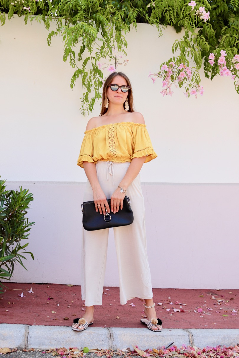 Pompon Straw Sandals. Fashion Blogger Girl by Style Blog Heartfelt Hunt. Girl with blond hair wearing a yellow off shoulder top, wide pants, tortoise shell sunglasses, tassel earrings, clutch and pompon straw sandals.