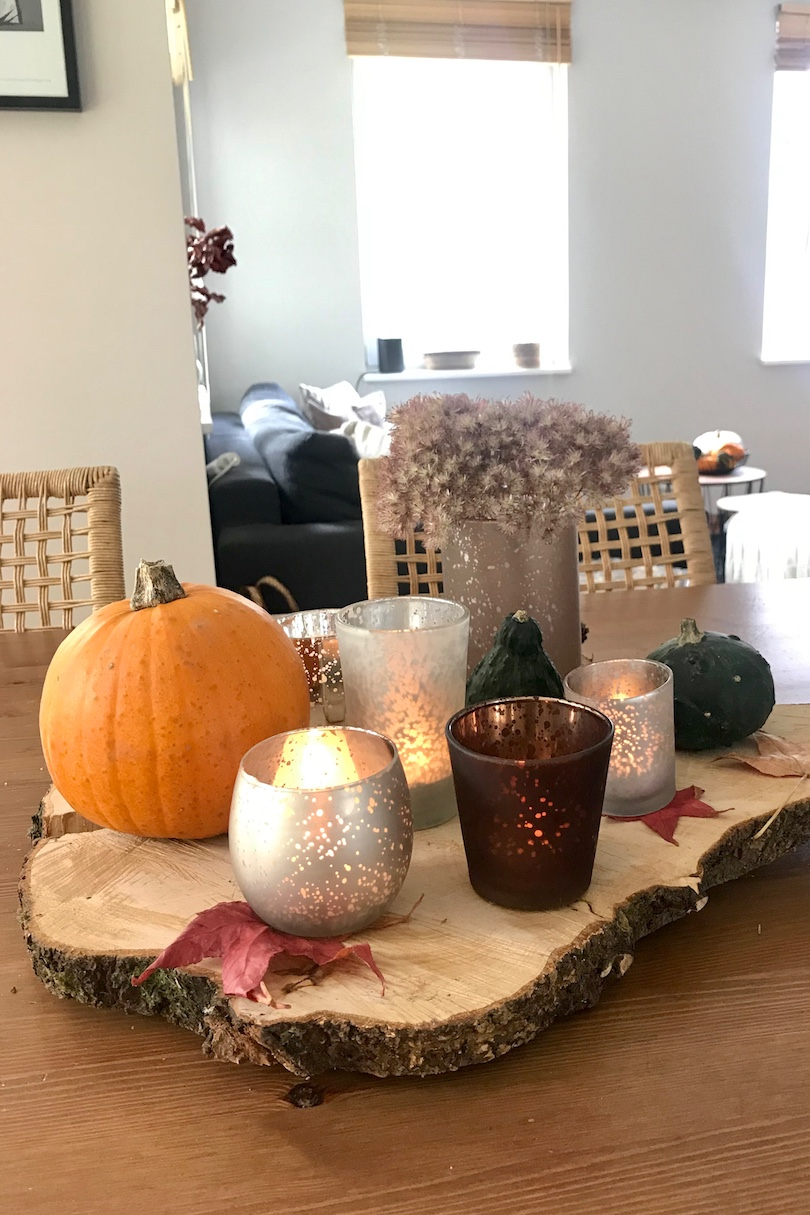 Pretty Fall Decor. Fashion Blogger Girl by Style Blog Heartfelt Hunt. Girl with blond, high ponytail wearing a checked dress and showing her pretty fall decor with velvet pillows and pumpkins.