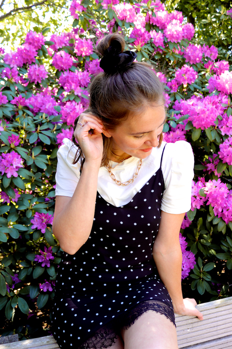 Purple Flower Rain. Fashion Blogger Girl by Style Blog Heartfelt Hunt. Girl with blond half-up half-down hairstyle and black velvet scrunchie wearing a polka dot slip dress, tee with puffed sleeves, statement necklace and Nike sneakers.
