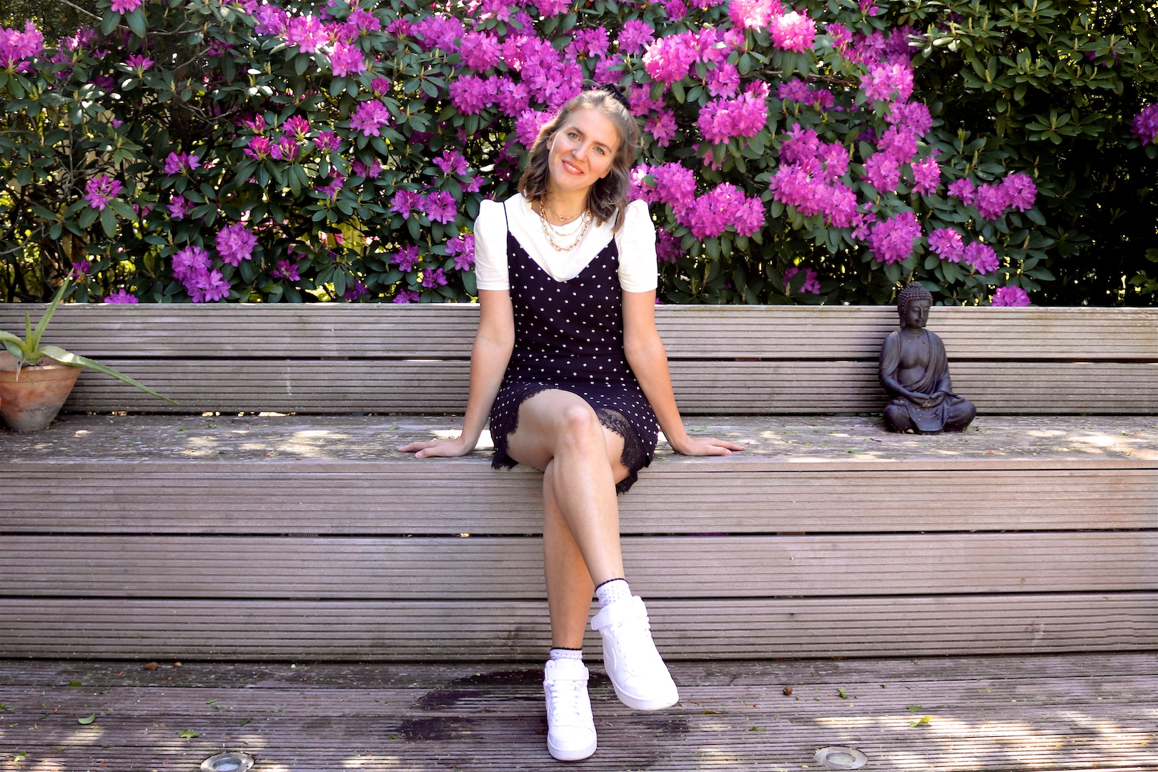 Purple Flower Rain. Fashion and Style Blog Girl from Heartfelt Hunt. Girl with blonde half-up half-down hairstyle and black velvet scrunchie wearing a polka dot slip dress, tee with puffed sleeves, statement necklace and Nike sneakers.