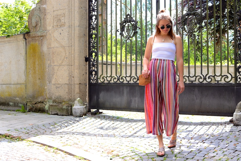Rainbow Pants. Fashion Blogger Girl by Style Blog Heartfelt Hunt. Girl with blond hair wearing a rainbow pants, white top, Ray-Ban sunglasses, straw bag and glittery sandals.