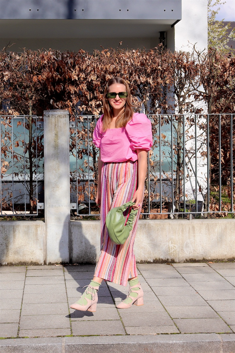 Rainbow Pants. Fashion and Style Blog Girl from Heartfelt Hunt. Girl with blonde hair wearing rainbow pants, pink puff sleeve blouse, green sunglasses, green ruched bag, green socks and pink heels.