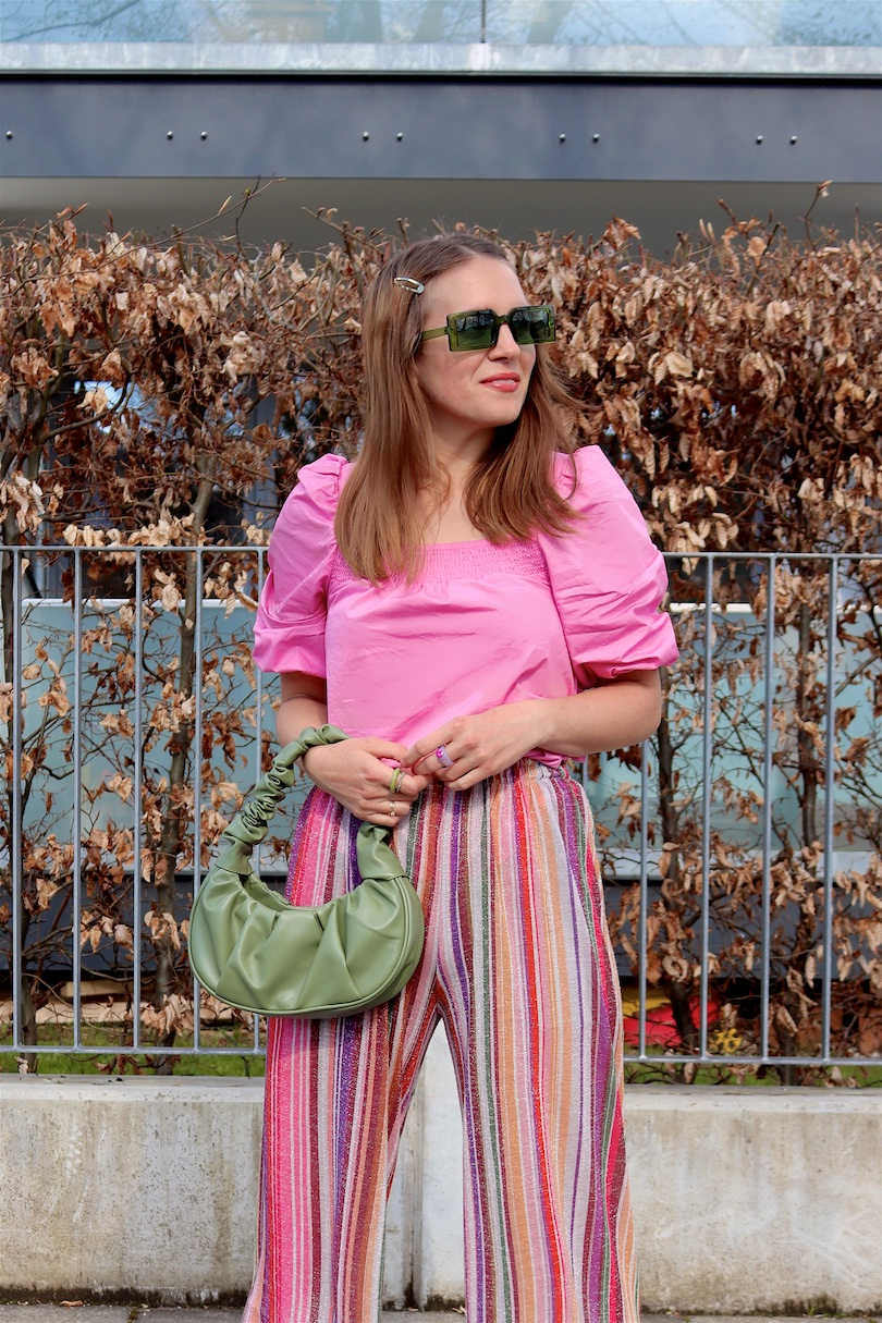 Rainbow Pants. Fashion Blogger Girl by Style Blog Heartfelt Hunt. Girl with blond hair wearing rainbow pants, pink puff sleeve blouse, green sunglasses, green ruched bag, green socks and pink heels.