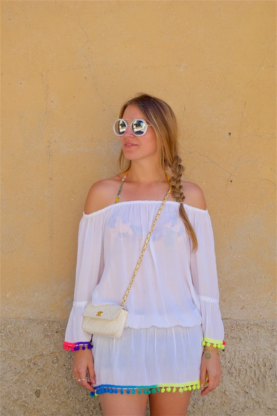 Rainbow Pompons. Fashion Blogger Girl by Style Blog Heartfelt Hunt. Girl with blond side braid wearing a top with rainbow tassels, denim shorts, bikini, sunglasses, vintage Chanel bag and glitter sandals.