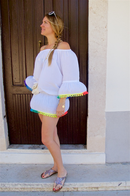 Rainbow Pompons. Fashion and Style Blog Girl from Heartfelt Hunt. Girl with blonde side braid wearing a top with rainbow tassels, denim shorts, bikini, sunglasses, vintage Chanel bag and glitter sandals.