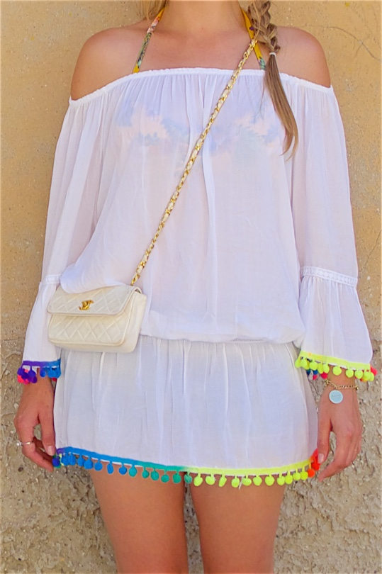 Rainbow Pompons. Fashion Blogger Girl by Style Blog Heartfelt Hunt. Girl with blond side braid wearing a top with rainbow tassels, denim shorts, bikini, vintage Chanel bag and glitter sandals.