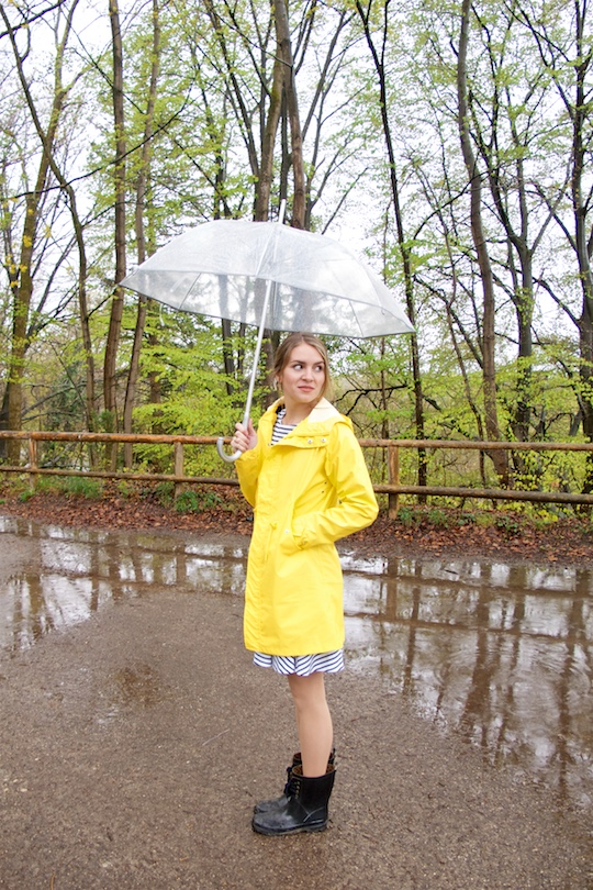 Rainy Days. Fashion Blogger Girl by Style Blog Heartfelt Hunt. Girl wearing a yellow raincoat, striped dress, black boots and an umbrella.