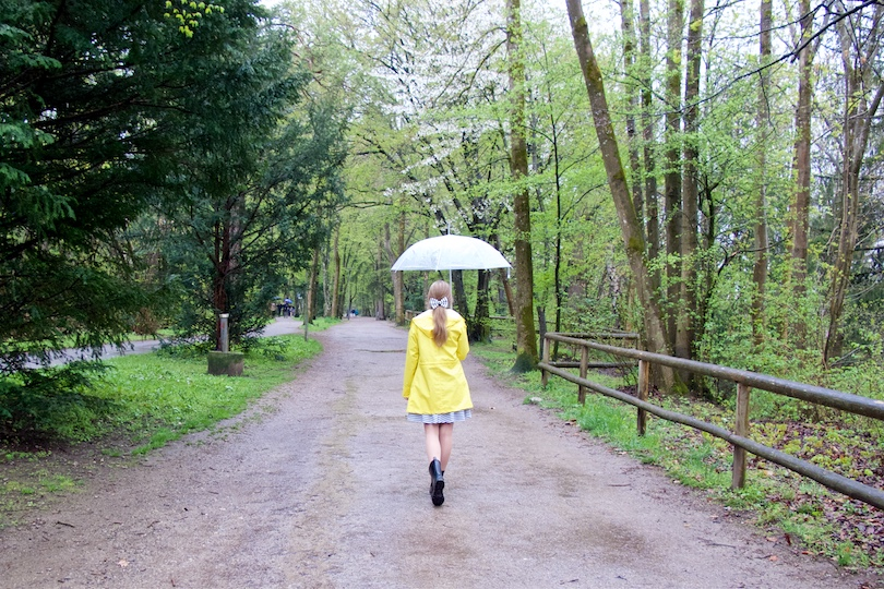 Rainy Days. Fashion and Style Blog Girl from Heartfelt Hunt. Girl wearing a yellow raincoat, striped dress, striped bow, black boots and an umbrella.