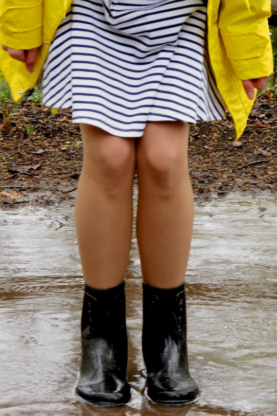 Rainy Days. Fashion and Style Blog Girl from Heartfelt Hunt. Girl wearing a yellow raincoat, striped dress and black boots.