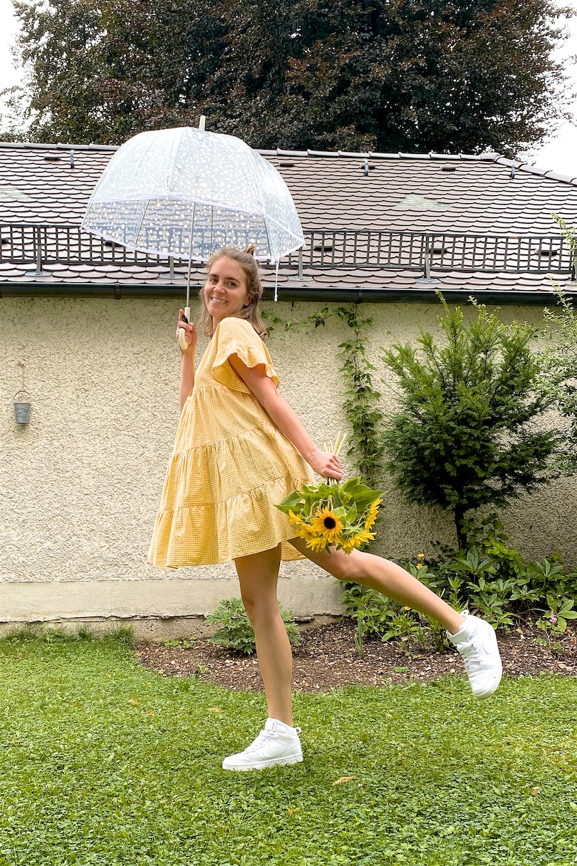 Rainy Summer Day. Fashion and Style Blog Girl from Heartfelt Hunt. Girl with blonde half-up half-down messy bun wearing a gingham dress and white Nike sneakers.
