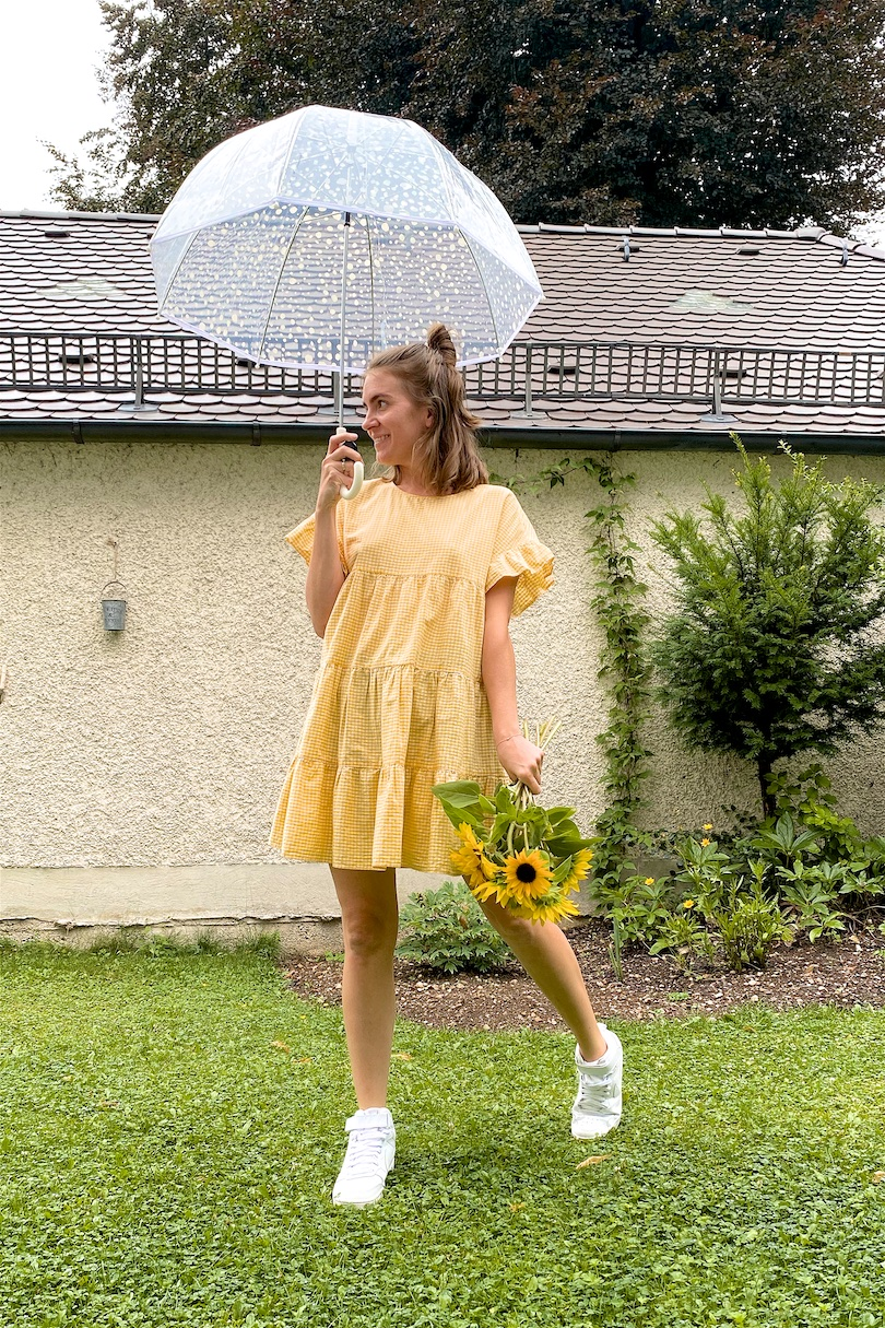 Rainy Summer Day. Fashion Blogger Girl by Style Blog Heartfelt Hunt. Girl with blond half-up half-down messy bun wearing a gingham dress and white Nike sneakers.