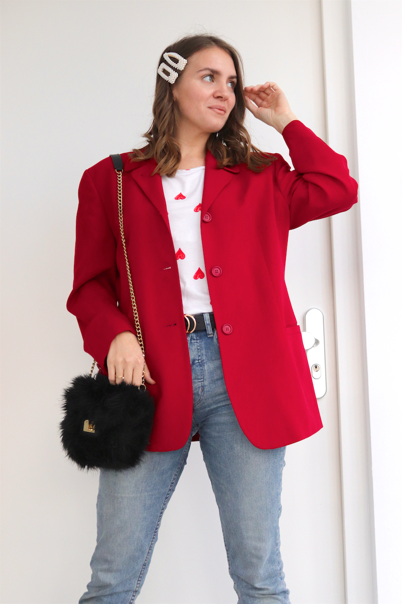 Red Blazer Hearts. Fashion and Style Blog Girl from Heartfelt Hunt. Girl with blonde, loose curls and pearl hair clips wearing a red blazer, hearts tee, mom jeans, faux fur bag, belt and faux fur chunky sneakers.