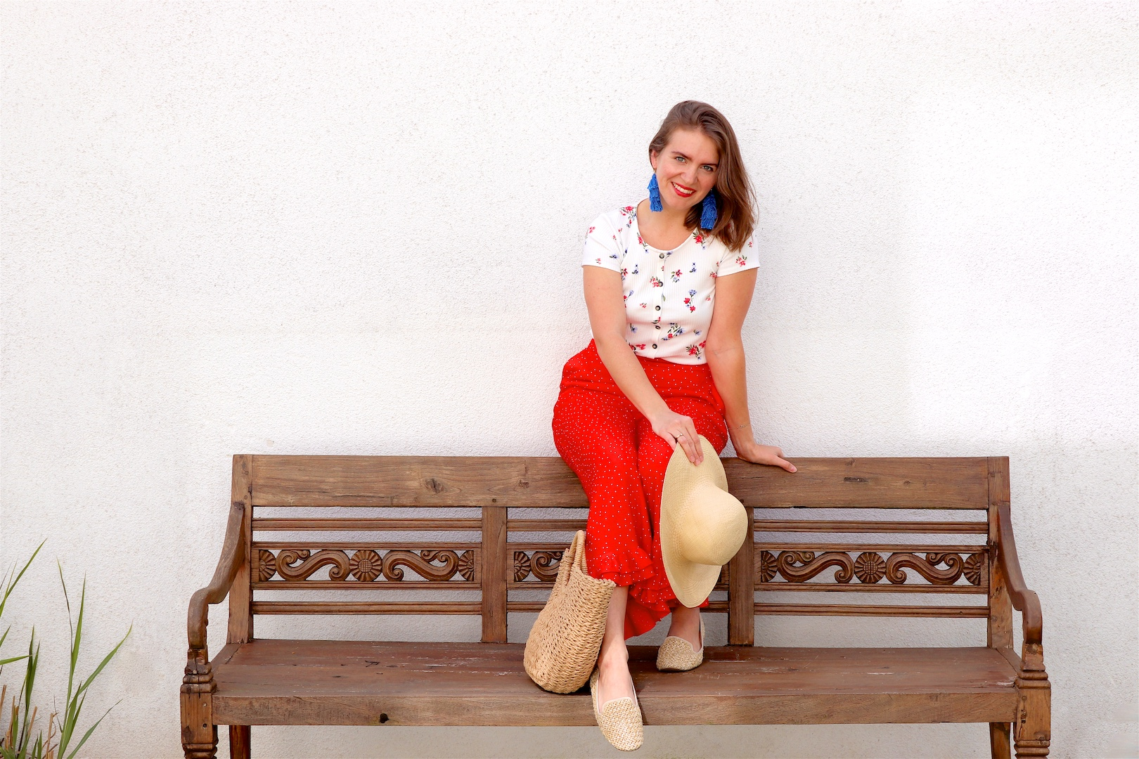 Red Floral. Fashion and Style Blog Girl from Heartfelt Hunt. Girl with blonde hair wearing a floral tee, red pants, blue tassel earrings, straw hat, straw bag and straw loafers.