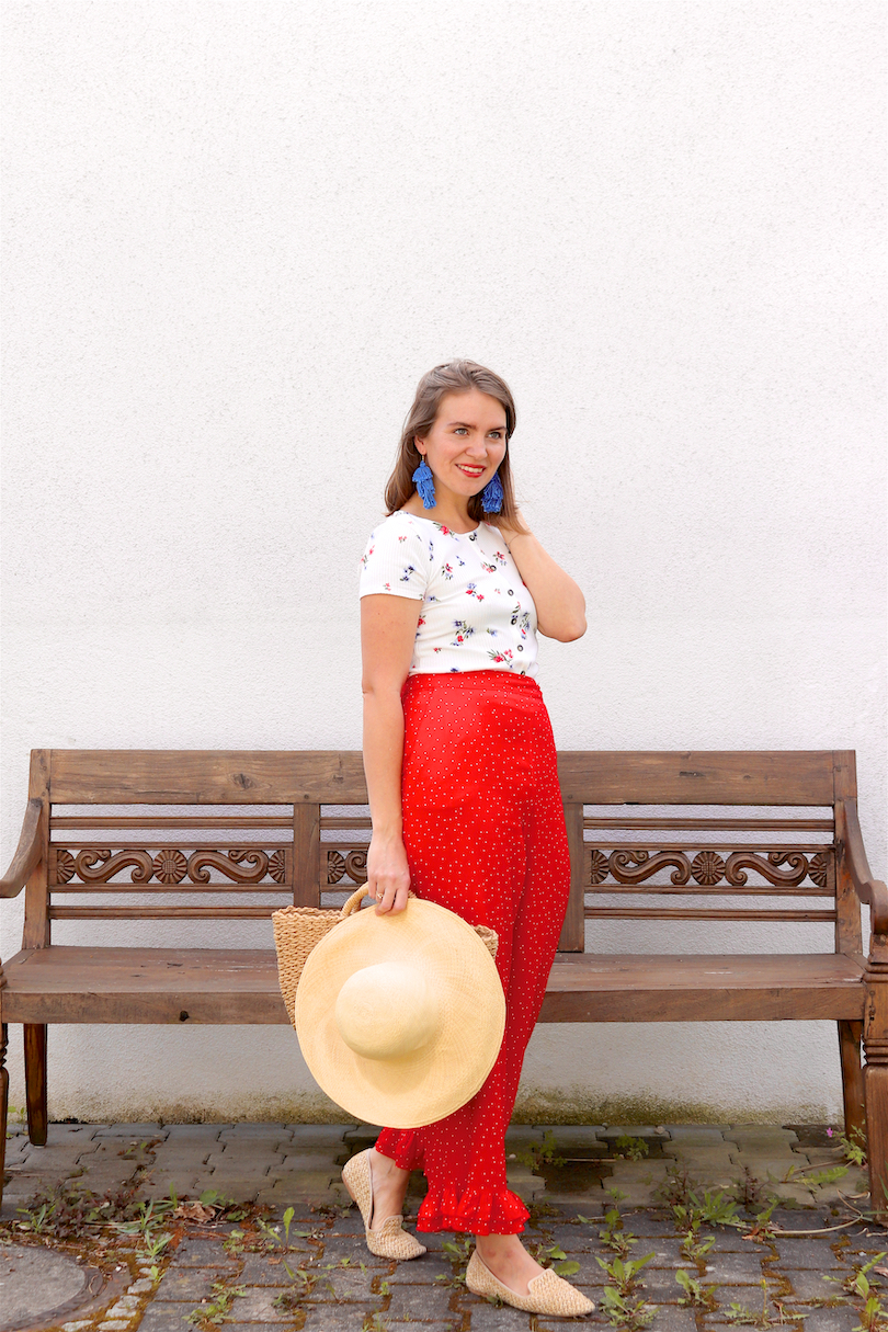 Red Floral. Fashion Blogger Girl by Style Blog Heartfelt Hunt. Girl with blond hair wearing a floral tee, red pants, blue tassel earrings, straw hat, straw bag and straw loafers.