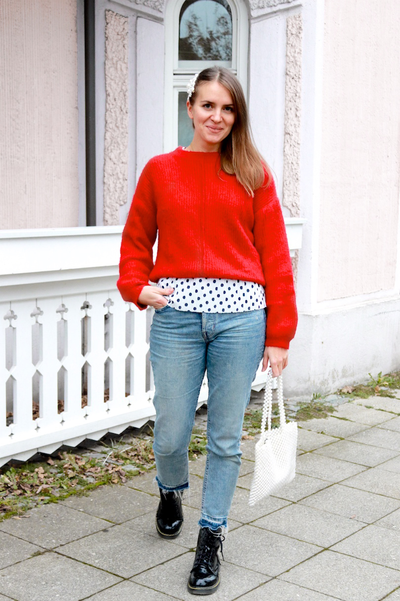 Red Polka Dots. Fashion and Style Blog Girl from Heartfelt Hunt. Girl with blonde hair and pearl hair clips wearing a red sweater, polka dot top, mom jeans, pearl bag and glossy boots.