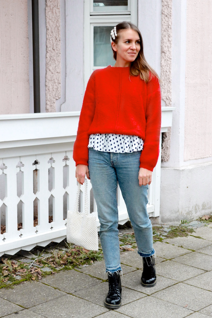 Red Polka Dots. Fashion Blogger Girl by Style Blog Heartfelt Hunt. Girl with blond hair and pearl hair clips wearing a red sweater, polka dot top, mom jeans, pearl bag and glossy boots.