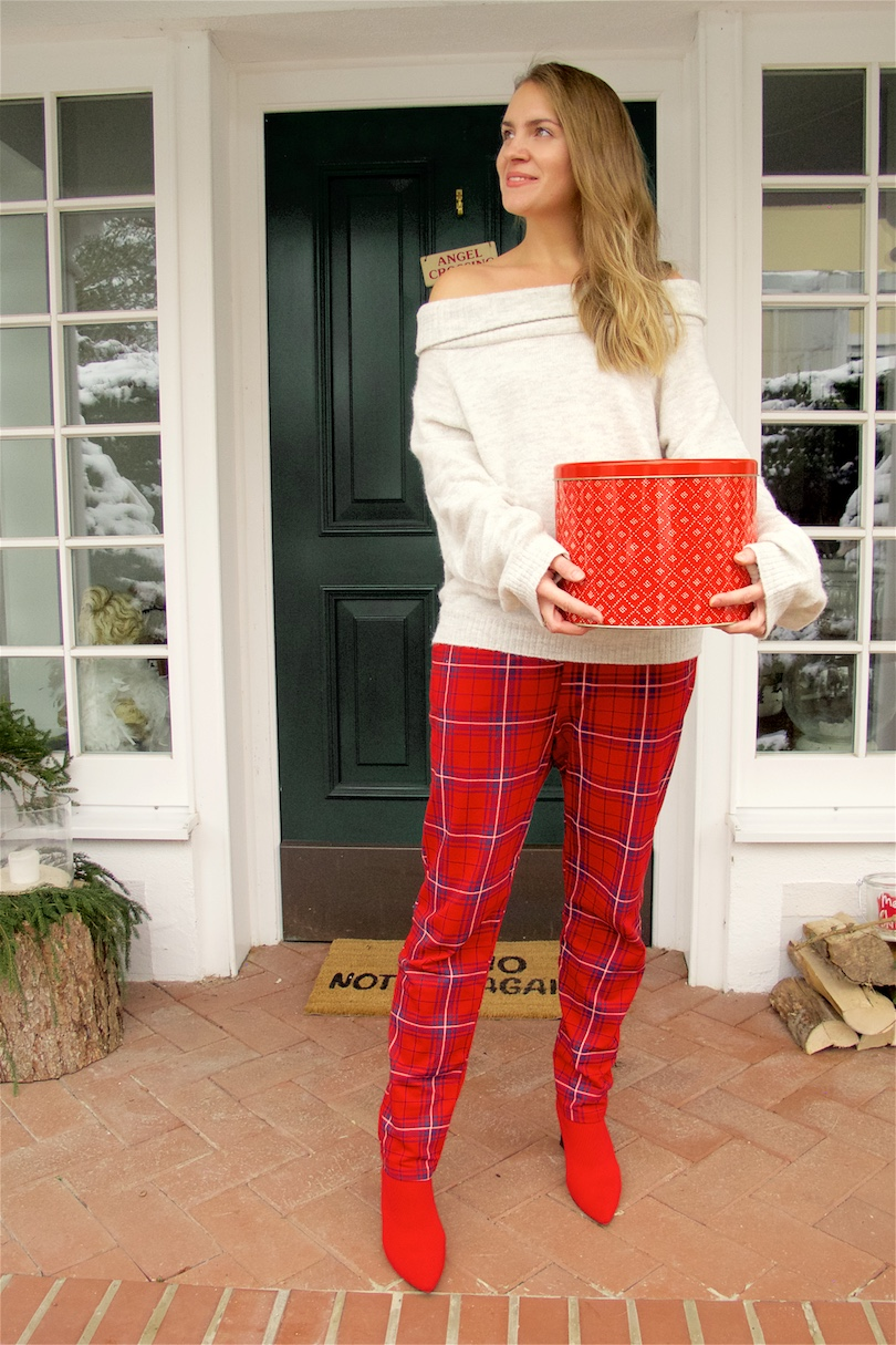 Red Tartan Pants. Fashion Blogger Girl by Style Blog Heartfelt Hunt. Girl with blond hair and a box for Christmas cookies wearing red tartan pants, off shoulder sweater and red sock boots.