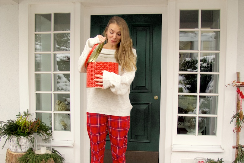 Red Tartan Pants. Fashion and Style Blog Girl from Heartfelt Hunt. Girl with blonde hair and a box for Christmas cookies wearing red tartan pants, off shoulder sweater and red sock boots.