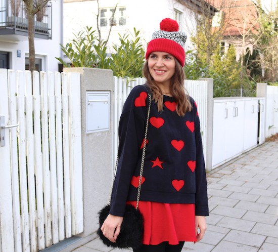 Romantic Holiday Season Look. Fashion Blogger Girl by Style Blog Heartfelt Hunt. Girl with blond, loose waves wearing a romantic sweater with hearts, red skirt, pompom beanie, faux fur bag and over the knee boots.