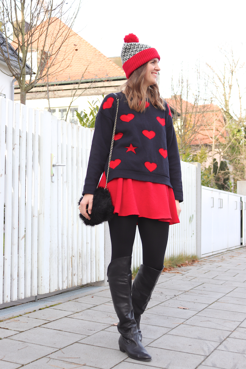 Romantic Holiday Season Look. Fashion and Style Blog Girl from Heartfelt Hunt. Girl with blonde, loose waves wearing a romantic sweater with hearts, red skirt, pompom beanie, faux fur bag and over the knee boots.