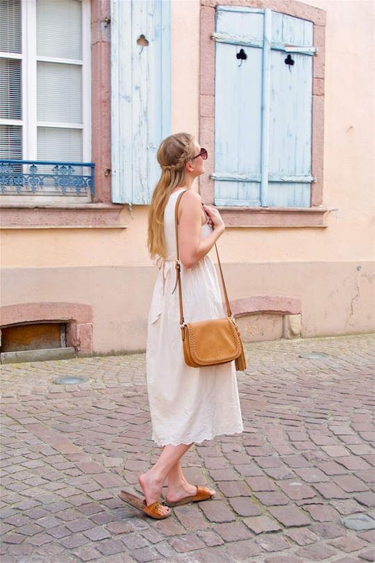 Romantic Pastel Colors. Fashion and Style Blog Girl from Heartfelt Hunt. Girl with braided half-up half-down hairstyle wearing a romantic lace dress, sunglasses, tassel bag and sandals.