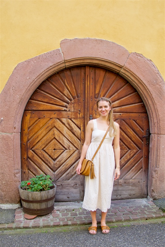 Romantic Pastel Colors. Fashion Blogger Girl by Style Blog Heartfelt Hunt. Girl with braided half-up half-down hairstyle wearing a romantic lace dress, tassel bag and sandals.