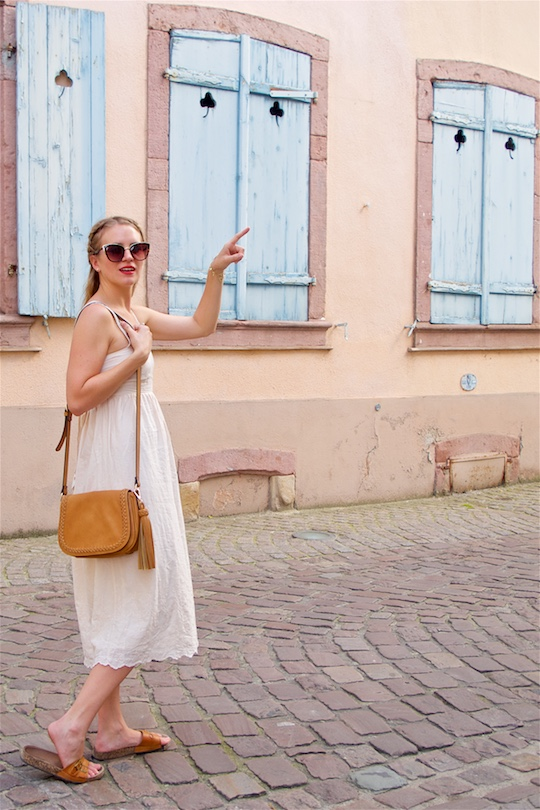 Romantic Pastel Colors. Fashion Blogger Girl by Style Blog Heartfelt Hunt. Girl with braided half-up half-down hairstyle wearing a romantic lace dress, sunglasses, tassel bag and sandals.