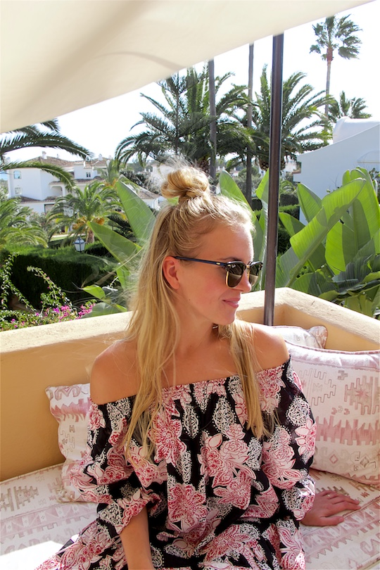 Roof Terrace. Fashion and Style Blog Girl from Heartfelt Hunt. Girl with blonde half-up half-down knot wearing an off-shoulder flower dress and Ray-Ban sunglasses.