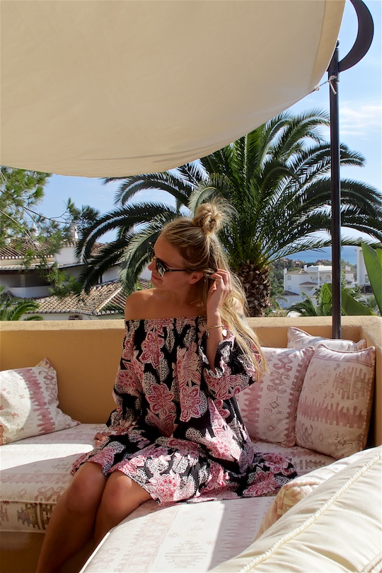 Roof Terrace. Fashion Blogger Girl by Style Blog Heartfelt Hunt. Girl with blond half-up half-down knot wearing an off-shoulder flower dress and Ray-Ban sunglasses.