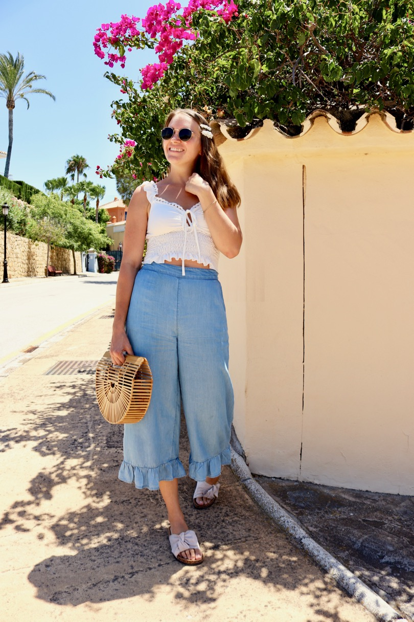 Ruffled Sleeves. Fashion Blogger Girl by Style Blog Heartfelt Hunt. Girl with blond hair and pearl hair clips wearing a top with ruffled sleeves, ruffled pants, Ray-Ban sunglasses, bamboo bag and sandals with bows.