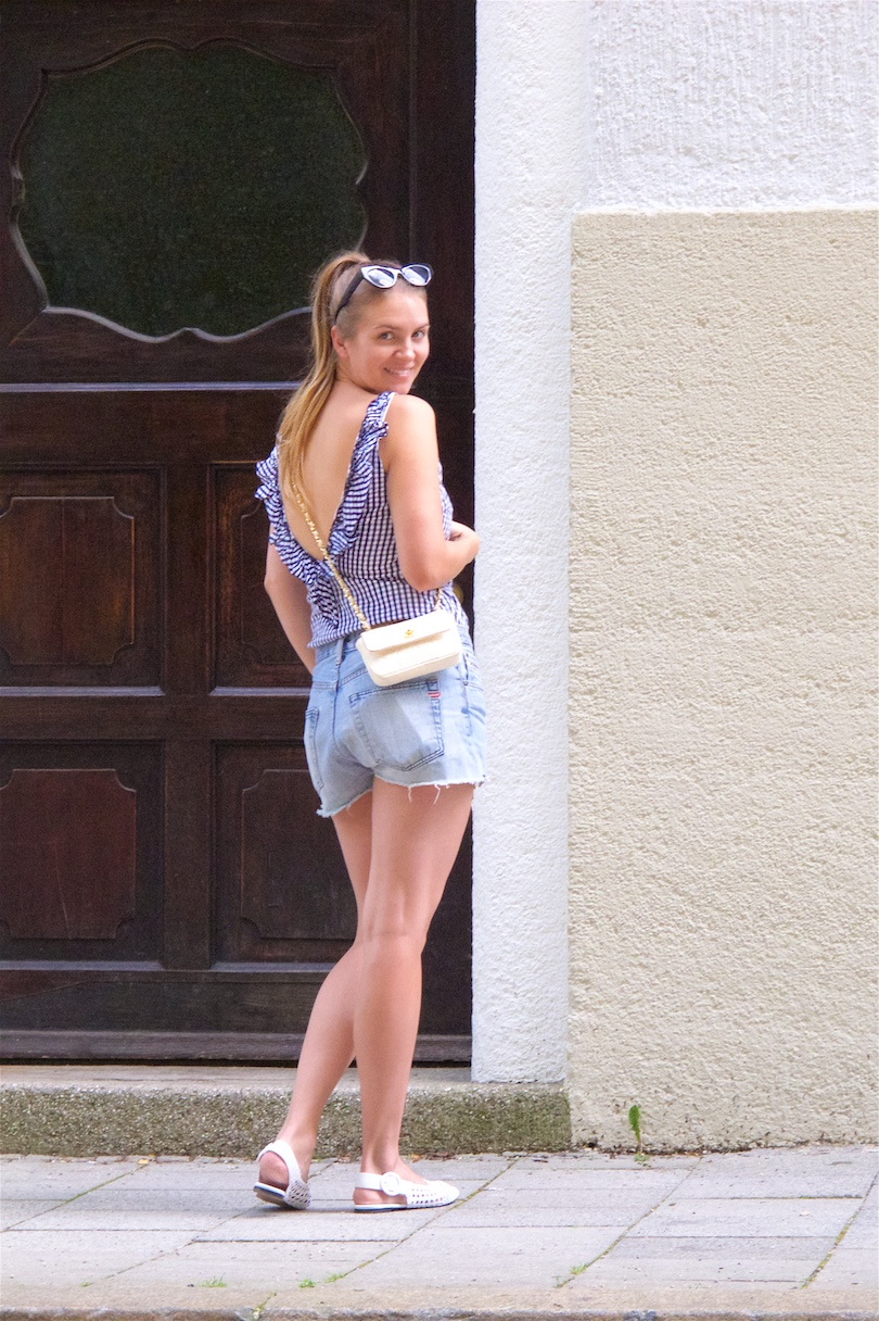 Ruffled Gingham. Fashion and Style Blog Girl from Heartfelt Hunt. Girl with blonde, high ponytail wearing a ruffled gingham dress as a top, denim shorts, vintage Chanel bag, slim sunglasses and slingback flat shoes.